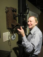 History Museum Director Jim Meinert demonstrates how an old wall phone was used.