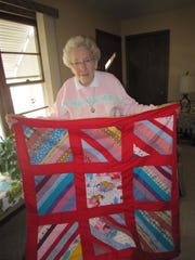 Betty shows off a small red blanket she has for sale or as a give-away.