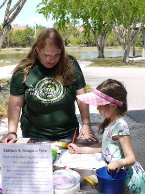 Carrie Nameth of Nature on Wheels shows a home school student how to record observations into her nature journal.
