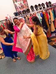 Indu Gupta and Tanya Gupta help arrange Sumanjit Kaur's sari. The 18-foot piece of fabric is carefully wound, pleated and tucked to fit the body of the wearer.