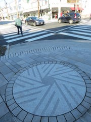 The Millstone motif is incorporated into the sidewalk at street corners in Millburn.