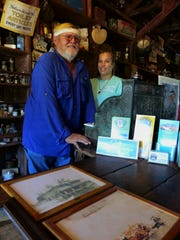 Gary McMillin and his daughter pose by the register inside the Smallwood Store-Museum on Chokoloskee Island on Dec. 22, 2016.