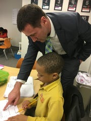 Academia Antonia Alonso Head of School Mark Phelps helps Omarr Alexander, a third-grader, with his classwork.