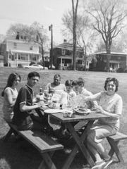 The Bouchard family are seen enjoying an alfresco lunch next to their home and business, the Bel-Aire Motel on Shelburne Street in Burlington, in this undated family photo.  The picnic table is where the Calahan Community Garden is now.