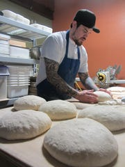 Matthew Carlson, baker and owner of Big Sky Bread & Pastry, shapes bread in his shop in 2013. He's announced he is closing the business at 4 5th St. S.