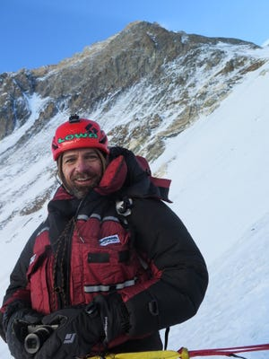 Fort Collins climber Jim Davidson takes a break at 23,200 feet, with the summit of Mount Everest behind him. Davidson reached the top of the world's highest peak May 22.