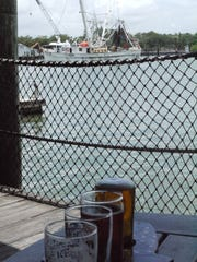 Shrimp trawler Big B sails past the open-air Dixie Fish Co., a waterfront restaurant that welcomes boaters.