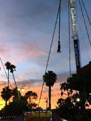 Roger Rodriguez, 19 of Oxnard, Calif., dangles from the cord of a bungee-jumping ride Aug. 2, 2017, that caused him to get stuck halfway between the ground and his starting point on the opening day of the Ventura County Fair in Ventura, Calif.