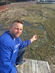 Michael Gutow crouches near a muck-infested section of Lake St. Clair shoreline in Macomb County's Harrison Township. Gutow is the creator of the Save Lake St. Clair Facebook page, which has nearly 25,000 followers.