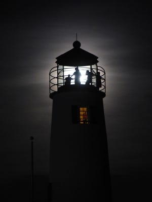 The Cape St. George Lighthouse is illuminated by an August full moon.