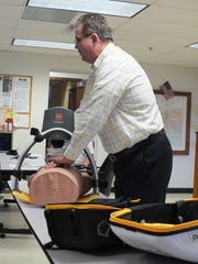 Jeff Preston, the senior sales rep for Physio-Control, Inc., the company which owns and distributes the LUCAS, demonstrates to the Franklin Fire Department how you can do chest compressions manually with the device attached. When one person is administering CPR, the other can attach the machine at the same time.