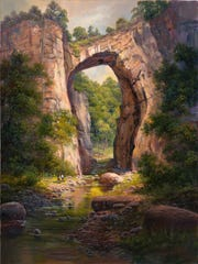 A natural bridge dwarfs George Washington, who, it is said, was able to smack the underside with a stone throw.