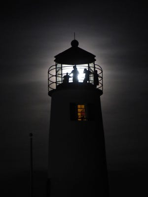 The Cape St. George Lighthouse is illuminated by the moon.