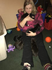 A submitted photo showing Carolyn Kirk, 28, holding a litter of puppies.