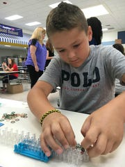 Jake DiGennaro, a fourth-grader in Shelby Dorr's class at Wilbur Elementary School, makes a bracelet to sell during Market Day for the student-designed Liberty Society.