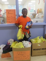 Third-grader Machai Morgan shows some of the 247 pounds of donations collected at Lafayette Elementary School in Bound Brook as part of the school district's Curbing Hunger Month food drive.