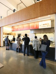 Customers waiting on line at a Chipotle restaurant