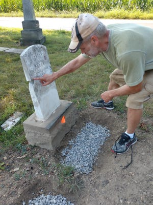 Ronny Echelberger shows the line of a broken cemetery stone be repaired in the Pine Run Cemetery on Hildebrandt Road in Worthington Township, Richland County.