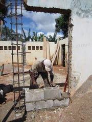 Bricklayer is one of 20 local volunteers building the first library in rural El Coyote village on the Samana Peninsula in the Dominican Republic, where Peace Corps worker Susan Stine of Merchantville has helped raise funds to build it, furnish it and supply books.