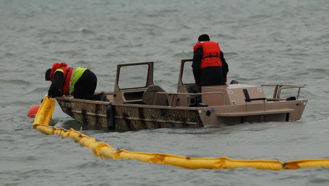 Enbridge employees place an oil containment boom in the St. Clair River near Marysville during a training exercise in 2016.