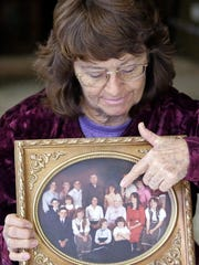 In this Dec. 16, 2014 photo, Katie Cox, a longtime Hildale, Utah, resident and member of the community's housing board, holds a photograph of her family in her home. Cox was one of two dozen people recently given the deeds to their houses. She said granting home ownership has offered hope that sect leaders will be unable to control people by way of their houses... It's a symbol of freedom. It's a symbol that we are part of this United States.""