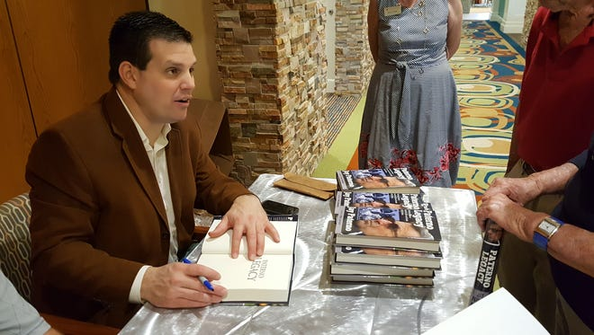 Jay Paterno, son of former Penn State football coach Joe Paterno, signs copies of his book about his father before speaking to the Southwest Florida chapter of the Penn State alumni association at Vi at Bentley Village on Tuesday, Feb. 20, 2018.