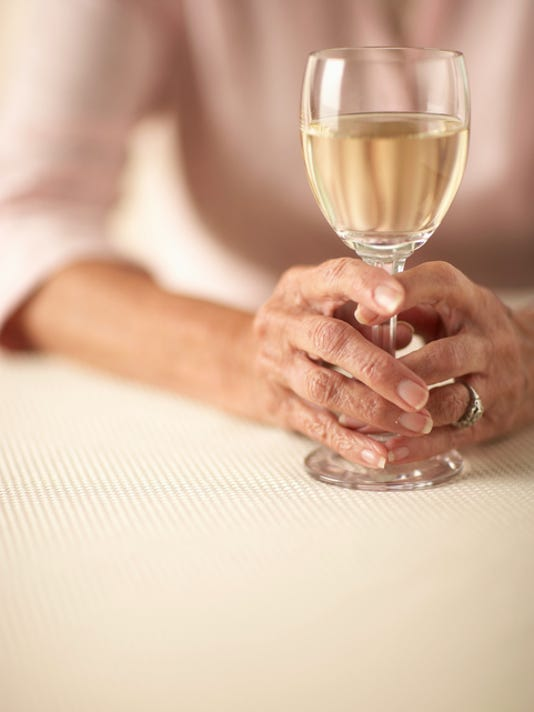 Senior woman sitting and holding glass of white wine, mid section, close-up of hands