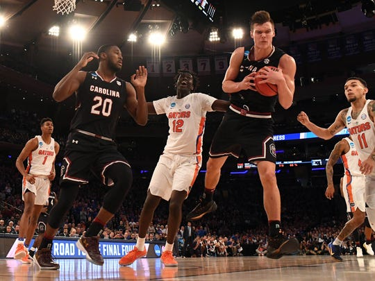 South Carolina Gamecocks forward Maik Kotsar (21) grabs a rebound against Florida Gators forward Gorjok Gak (12) during the second half in the finals of the East Regional of the 2017 NCAA Tournament at Madison Square Garden.