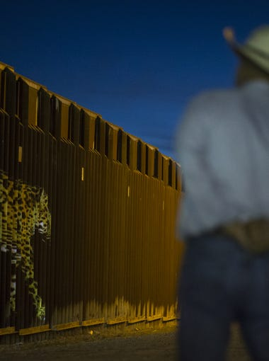 """An image of a jaguar is projected on the border wall in Douglas on May 12, 2017. Eco-political artist Lauren Strohacker used camera-trap photographs from the Northern Jaguar Reserve for the """"Un-fragmenting/Des-Fragmentando"""" event."""