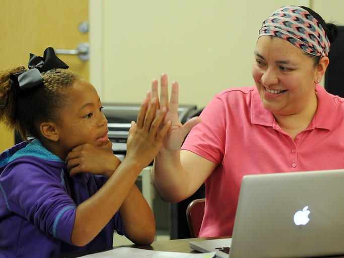 Chole Thompson, 10, receives a high-five Wednesday from iChallenge technology teacher Elvira Deyamport after completing an exercise during the program at N.R. Burger Middle School.