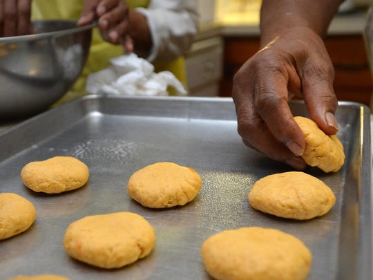 Ardella Ballard, 98, of Dublin, Md., and her daughter, Martha Ellen, form biscuits. Ballard prefers the ease of forming sweet potato biscuits by hand rather than cutting them out because of the thickness of the dough.