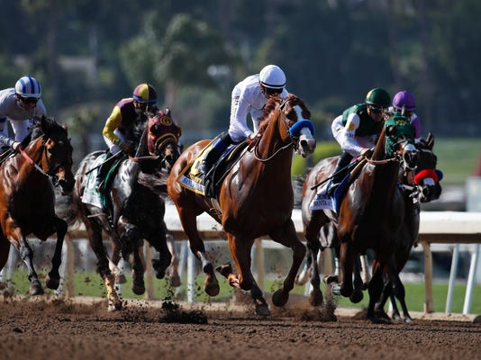 Justify, center, with jockey Mike Smith aboard, leads the pack during the Santa Anita Derby horse race at Santa Anita on Saturday, April 7, 2018, in Arcadia, Calif. Justify won the race. (AP Photo/Jae C. Hong)