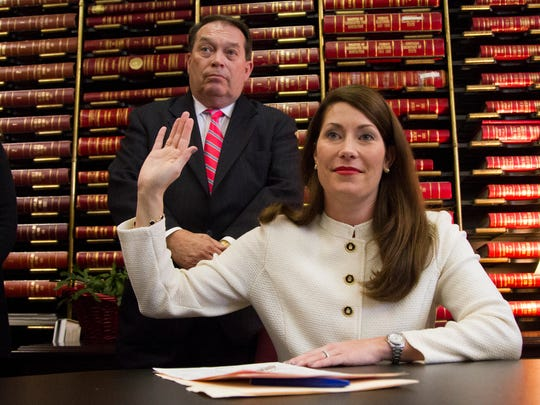 Kentucky Secretary of State Alison Lundergan Grimes takes an oath alongside her father Jerry Lundergan after filing for re-election of Secretary of State in the Office of Elections at the Kentucky State Capitol in Frankfort, Ky.   January 26, 2015.