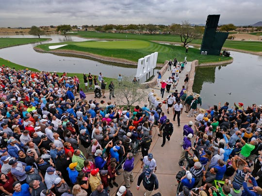 Golfers take in the action near the 15th hole of the