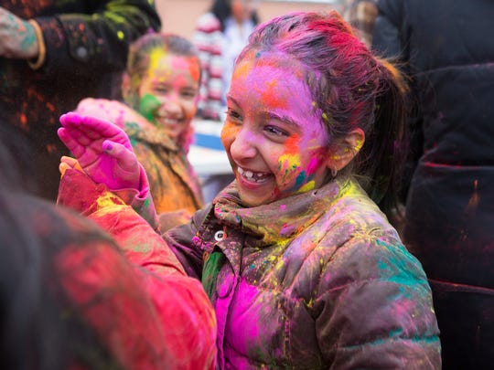 Priyanka Malhotra laughs with friends during a Holi celebration at the Hindu Temple of Rochester in Henrietta on Sunday, March 8, 2015.