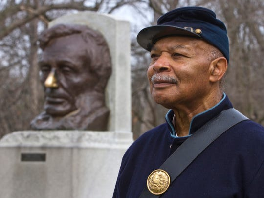 In this Wednesday, April 8, 2015 photo, Robert Davis, a Civil War re-enactor, poses for a portrait outside the tomb of Abraham Lincoln with a bust of Lincoln in the background in Springfield, Ill. As a boy in Detroit, he heard his elders talk of his great grandparents' life after slavery and the family's migration. In his spare time, he dons the Union uniform to join Civil War re-enactments, playing a runaway slave who joined the United States Colored Troops. (AP Photo/Randy Squires)