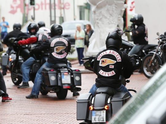 """Members of the Hells Angels motorcycle gang wear gear with the club's logo and read """"Latvia"""" (front) as they arrive for a funeral in Ransbach-Baumbach, western Germany on August 8, 2013."""