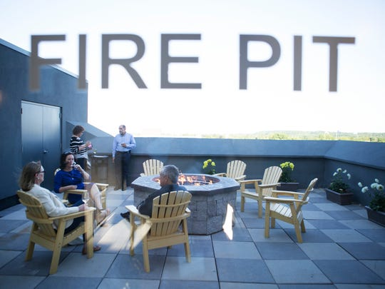 Guests enjoy drinks around the fire pit during the grand opening of the rooftop space at the Strathallan Hotel on Wednesday, June 3, 2015.