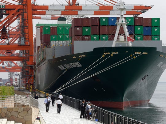 People walk in front of a container ship docked at a container terminal in Tokyo. The stakes in a U.S./Japan trade pact are meaningful: Japan is the fifth-biggest market for U.S. dairy, with $270 million in exports last year.