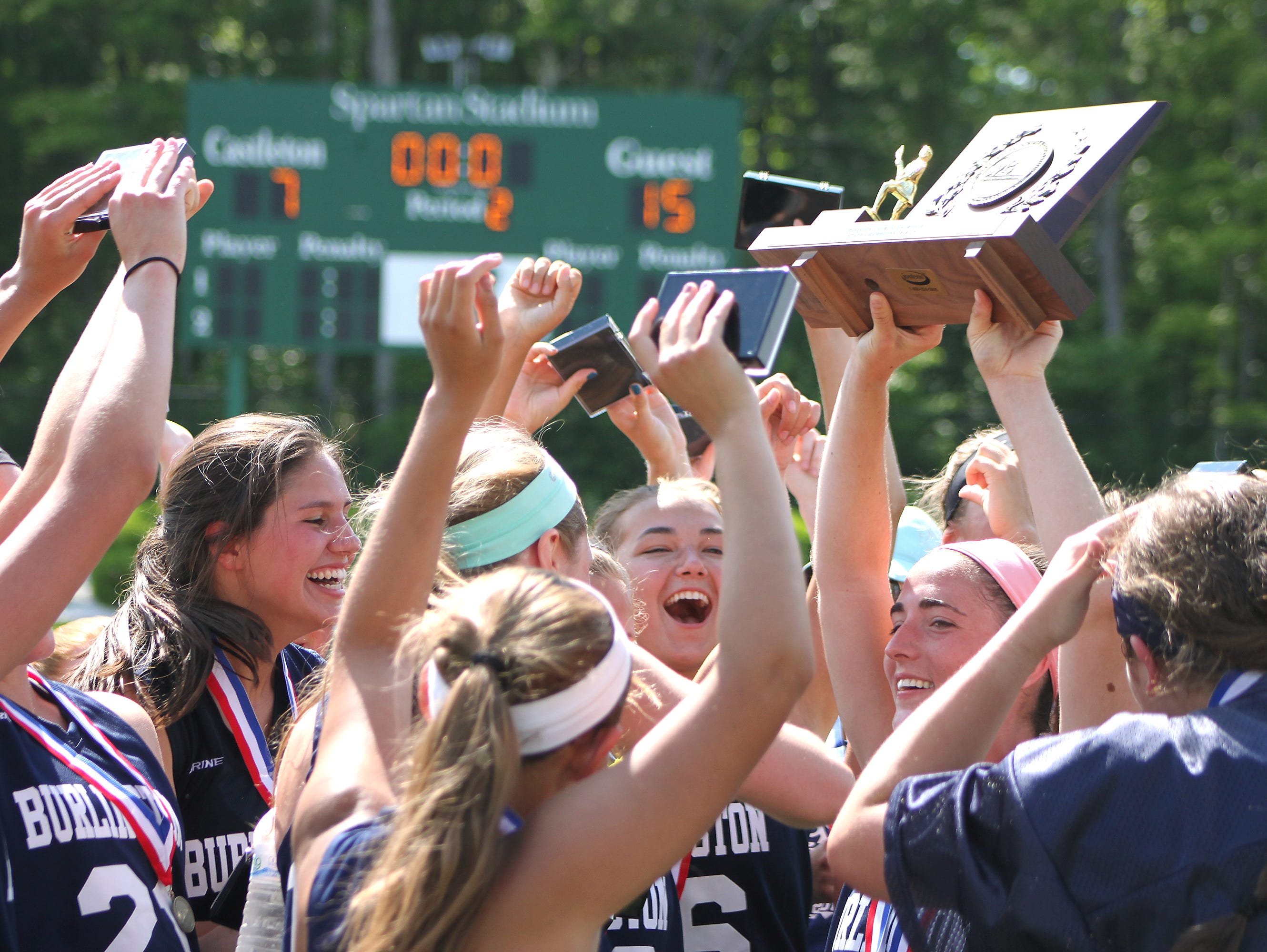The Burlington High School girls lacrosse team celebrates its first state championship after beating Burr and Burton 15-7 in the Division I final on Saturday at Castleton State College.
