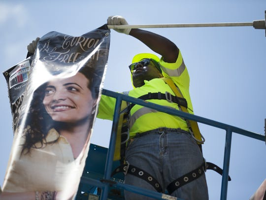 Al Castle with the City of Rochester hangs a banner for the Xerox Rochester International Jazz Festival along East Ave. in preparation for the festival on Thursday, June 18, 2015.