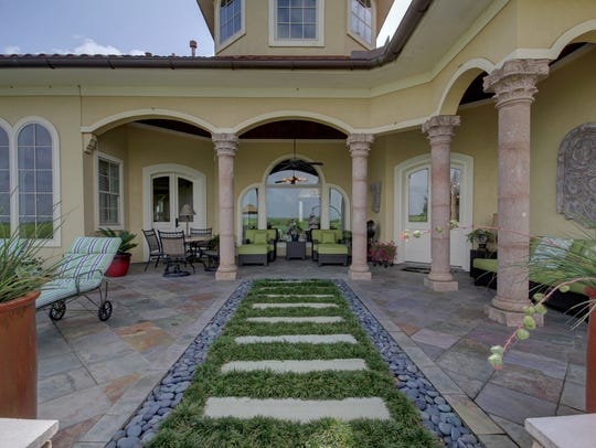 A formal garden and patio grace the back of the home