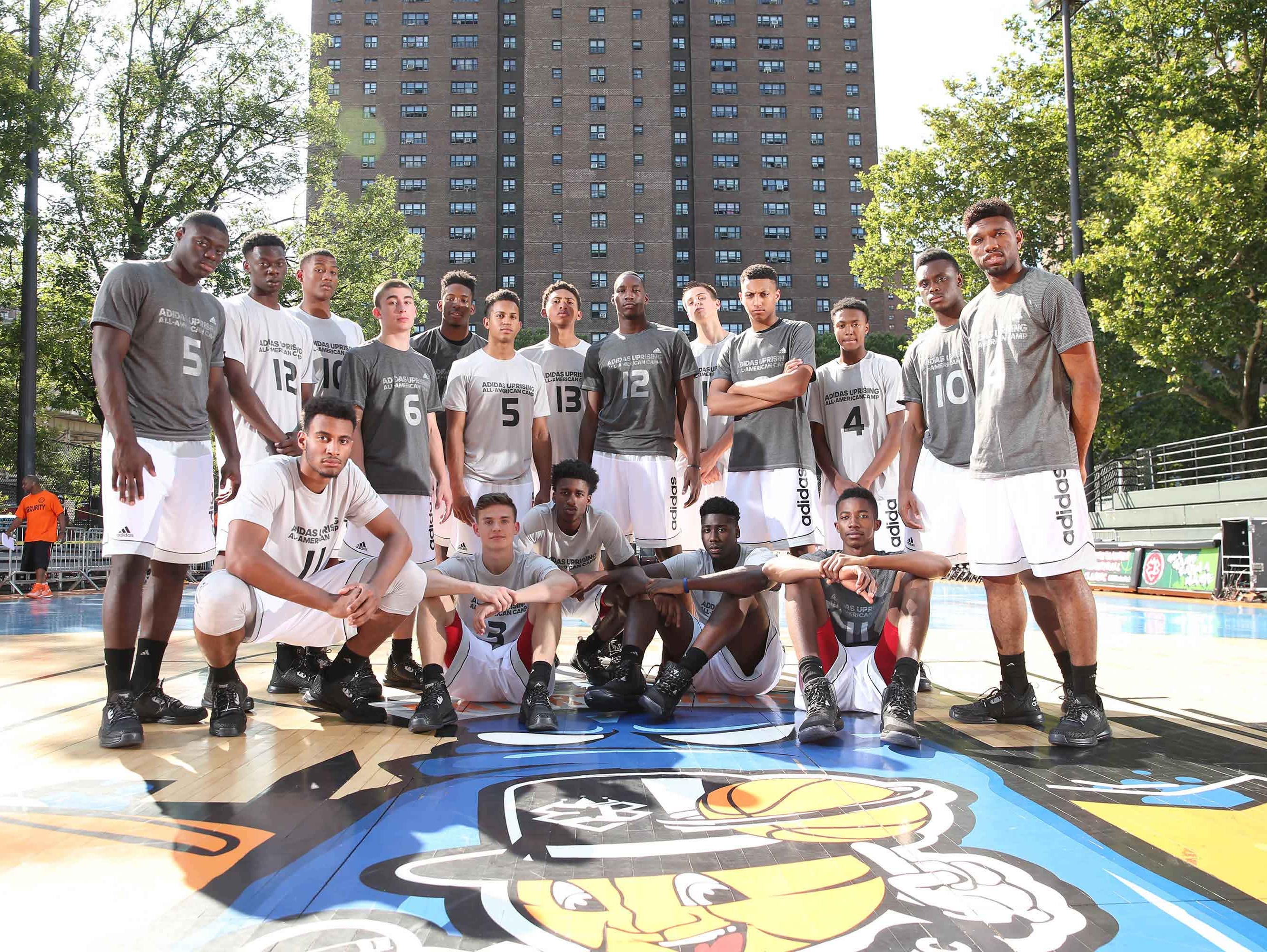 Eron Gordon (standing, far right) and Kyle Guy (seated, second from left) played on Thursday at Rucker Park