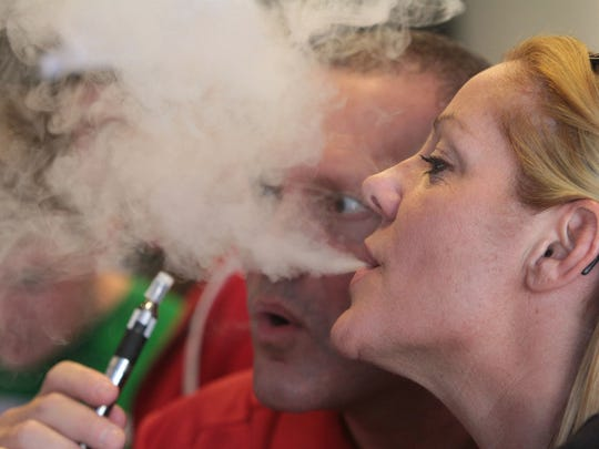 Janet Marsico and Lou Pasquin use her vaping device as she samples different flavors of e-liquids available at White Plains Vapors. The Food and Drug Administration will propose rules for e-cigarettes, which can have big implications, if approved, on a fast-growing industry and its legions of customers.