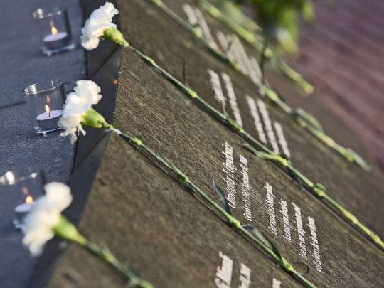Flowers lay near the names of Westchester County residents