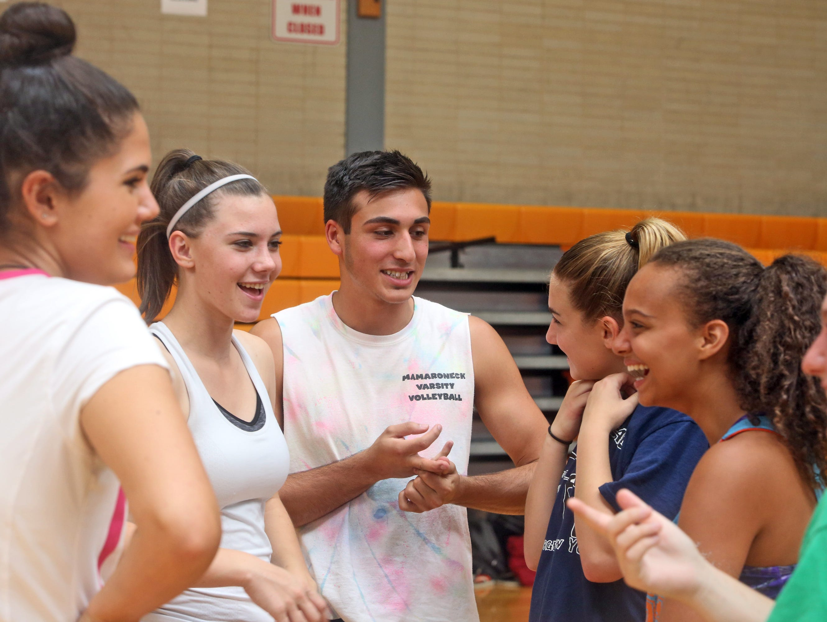 Andreo Otiniano, a senior at Mamaroneck High School, and a member of the girls volleyball team, talks with his teammates during practice Sept. 16, 2015. Otiniano played with the team as a sophomore, and still practices with the team and is on the roster, but present Section 1 rules do not allow him to play in matches.