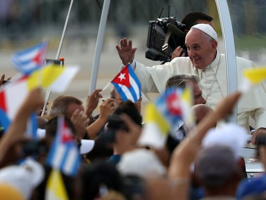 Carl Court, Getty Images HAVANA, CUBA - SEPTEMBER 20:  People wave Cuban and Papal flags as Pope Francis passes by as he arrives to perform Mass on September 20, 2015 in Revolution Square in Havana, Cuba. Pope Francis is on the first full day of his three day visit to Cuba where he will meet President Raul Castro and hold Mass in Revolution Square before travelling to Holguin, Santiago de Cuba and El Cobre then onwards to the United States.  (Photo by Carl Court/Getty Images) ORG XMIT: 579291645 ORIG FILE ID: 489322310
