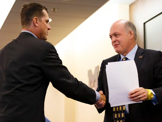 Dec 30, 2014; Ann Arbor, MI, USA; Jim Harbaugh shakes hands with Michigan Wolverines interim athletic director Jim Hackett as he is introduced as the new head football coach at Jonge Center. Mandatory Credit: Rick Osentoski-USA TODAY Sports