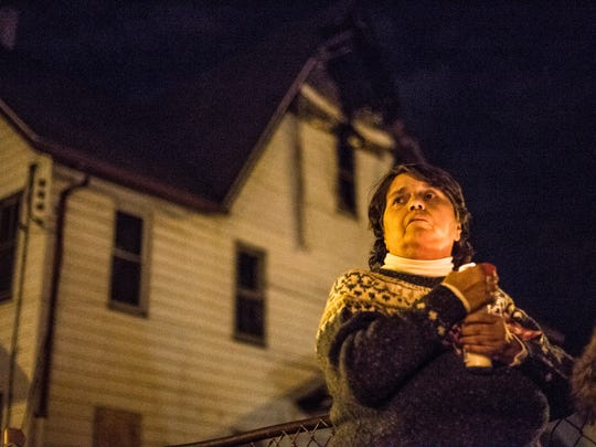 Lorraine Bailey, of Windsor, holds a candle during a vigil held for the victims of an arson fire at 145 Floral St. in Johnson City on Monday evening. Bailey says her daughter went to school with the mother of the two boys who were killed.