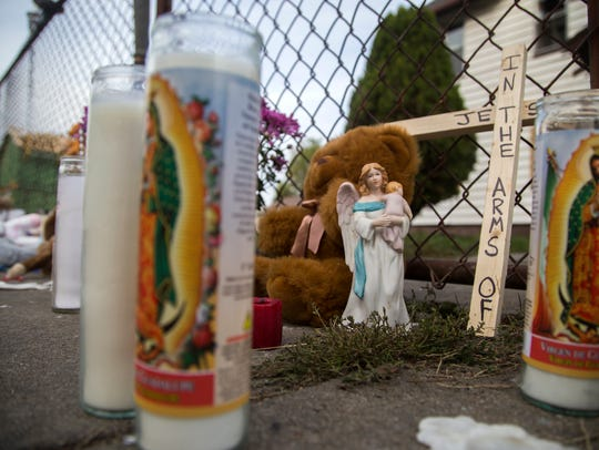Several candles remained lit Tuesday morning at the
